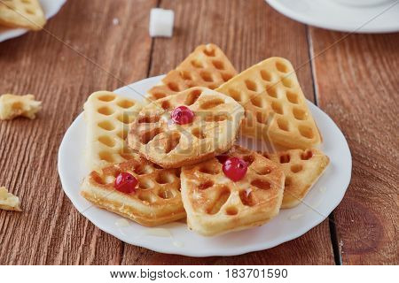 Freshly baked waffles and coffee on a wooden background