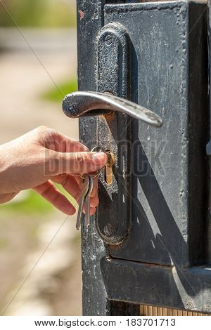 Woman opens the metal door using the key. Selective focusing