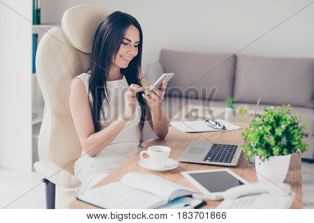 Close Up Portrait Of Young Brunette Woman Typing An Sms On Her Pda While Having A Coffee Break At Wo