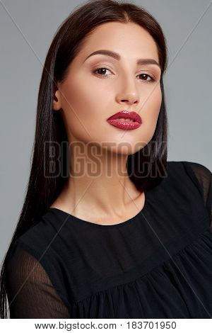 Beautiful woman face close up portrait young studio on gray. Woman in black dress