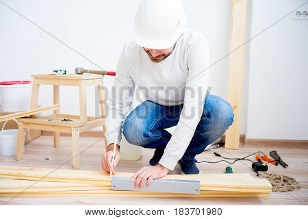 Craftsman measuring wooden plank with ruler and pencil