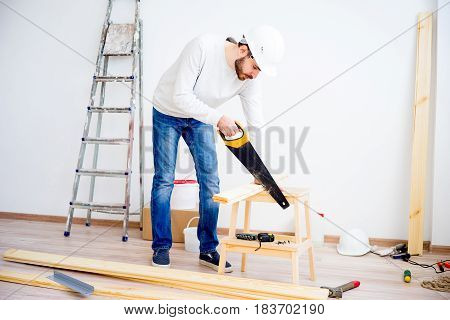 A male carpenter with a handsaw at a workshop