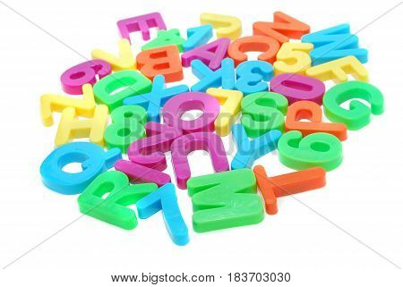 Heap of Colored English Alphabet Letters and Digits Isolated on White