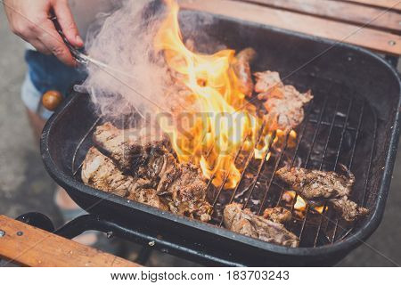 Grill steaks on metal grate with flame. Chef hands cooking roasted juicy meat barbecue with lots of fire. BBQ fresh beef chop slices.