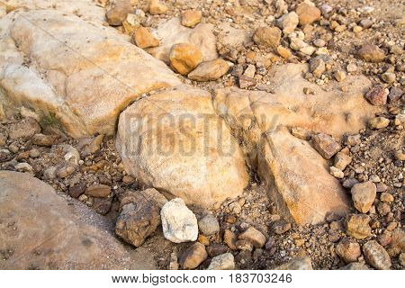 small rock formation in brown tones with lose rocks