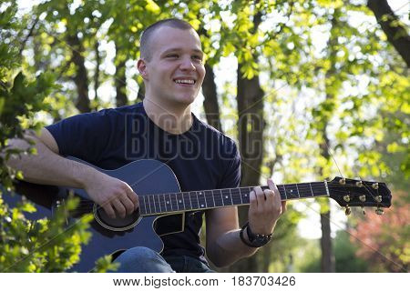 Portrait Of A Young Man With Guitar In The Park
