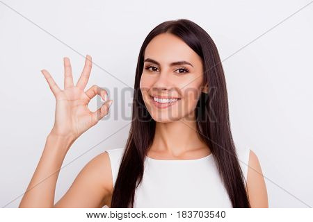 Happy Cute Brunette Girl Is Showing Ok Gesture And Smiling. She Is In White Dress On The Snow White