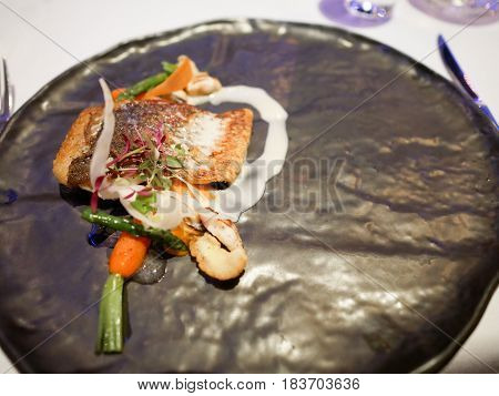 Grilled fish dish in fine dining restaurant.