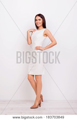 Portrait Of Elegant Cute Smiling Lady, Standing On A White Backgroung. She Is Wearing White Nice Dre