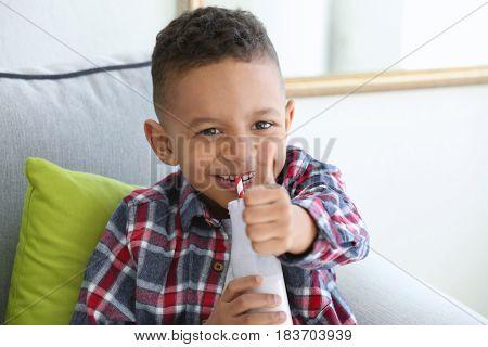 Cute African American boy drinking yogurt at home