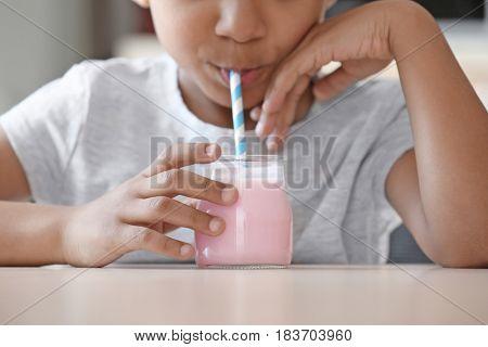 Cute African American boy drinking yogurt at home, closeup