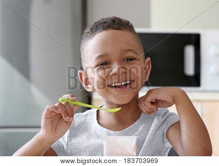 Cute African American boy eating yogurt at home