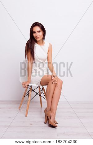 Full Size Portrait Of Young Businesslady. She Is Wearing Formal White Stylish Dress And High Hills S