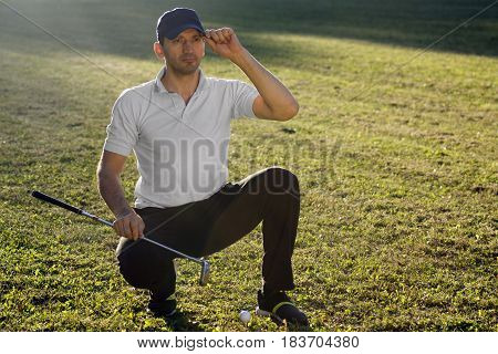 The golf player is looking away on playing field.