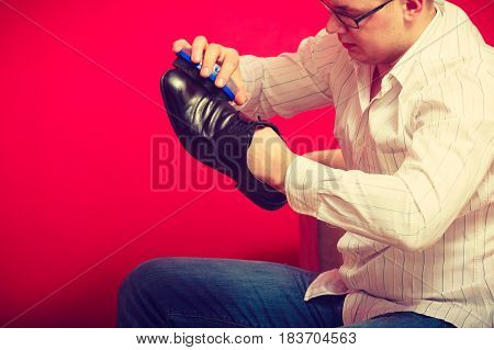 Footwear and man fashion gentleman outfit concept. Guy cleaning and polishing black elegant shoes