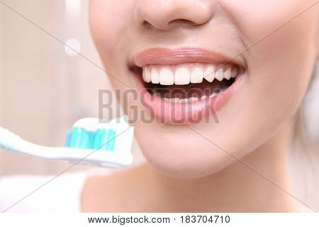 Beautiful woman brushing teeth, closeup