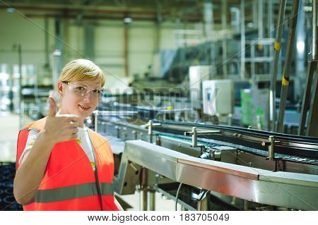 Portrait Female Employee In Orange Robe Vest In Working Space Of Production Facility, Supervises And