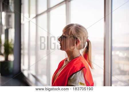 Portrait Of A Female Employee In An Orange Robe Vest In The Working Space Of A Production Room, Agai