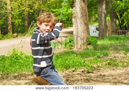 A boy is riding a rope swing