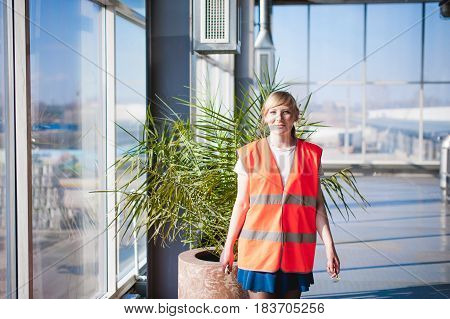 Female Employee In Orange Robe Wearing Vest In Working Space Production Room, Against Background Lar