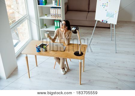 Top-view Of Young Successful Woman In Glasses Sitting At Table With Laptop, Cup Of Coffee In Office