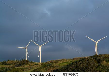 Power wind mills in a green hill against hazy sky in Portugal.