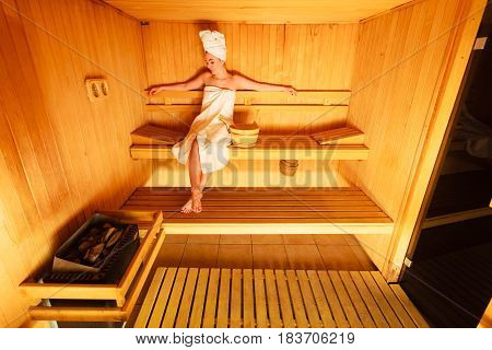 Woman Sitting Relaxed In Wooden Sauna