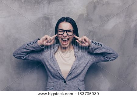 Portrait Of Uncontrollable Mad Girl Screaming And Closing Her Ears With Fingers