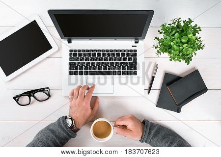 Directly above view of human hands typing on laptop. Laptop, digital tablet, diary, coffee cup and potted plant on work desk. Man working from home. poster