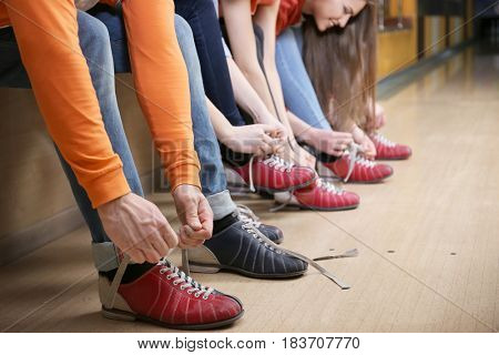 Group of young people changing their shoes in bowling club