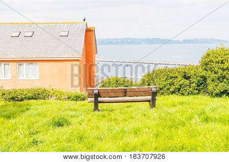 Empty Bench On The Hill, View Of The Harbor And Seaside Town