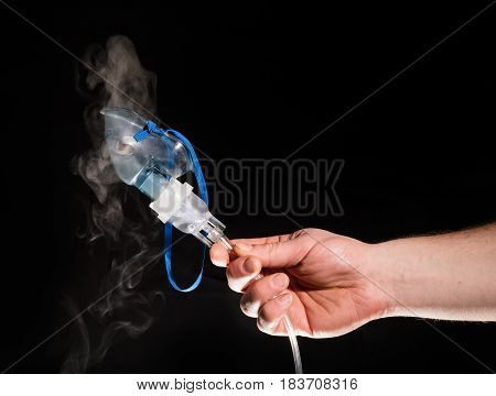 Man holding nebulizer mask with vapour on black background