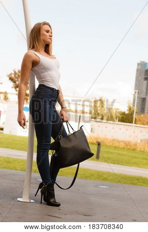 Fashion of female idea. Urban style. Stylish fashionable beauty woman with black bag handbag. Blondie girl model posing outside.