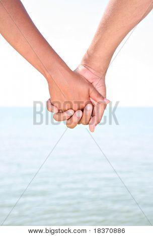 Zwei Jugendliche, die Hand in Hand mit Wasser als Hintergrund