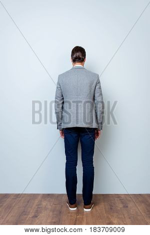 Vertical Back View Full-length Portrait Of Man In Gray Jacket And Dark Blue Trousers Standing Agains