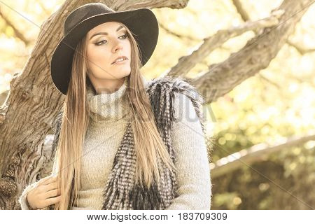Young beauty woman wearing stylish autumnal clothes relaxing in park. Portrait of fashionable caucasian girl student resting on air.