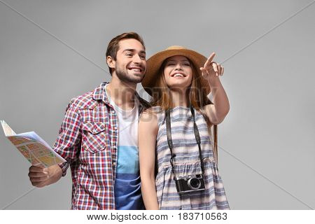 Couple of travelers with map on color background