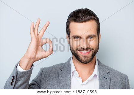 Close Up Photo Of Happy Man With Stylish Hairdo And In Formalwear Showing Ok-sign On Gray Background