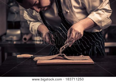 Chef cutting the fish on a board. Photo in brown tones. Kitchen. Wooden table