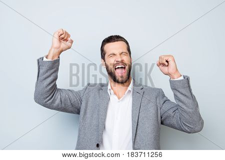 Yes! Young Excited Screaming Man In Suit With Raised Hands Depicted On Gray Background