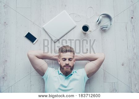 Overhead View Of Calm Man In Casual Clothing Lying On The Floor And Having A Rest After Work