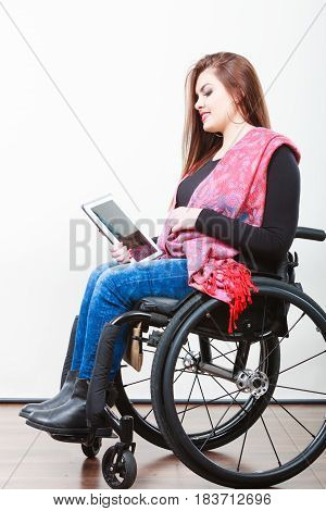 Young disabled lady with tablet. Girl on wheelchair surfing on internet. Health disability hobby internet technology concept.