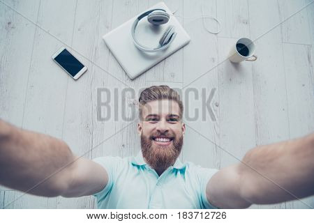 Handsome Bearded Young Man Is Making Selfie And Smiling. He Is In Light Blue T Shirt, His Belongings
