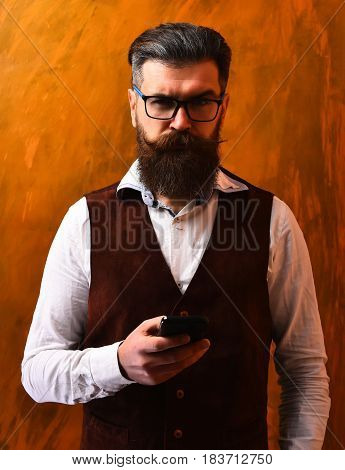 Bearded man long beard. Brutal caucasian unshaven serious hipster with glasses and moustache surfing internet on cell phone wearing white shirt suede waistcoat on brown studio background