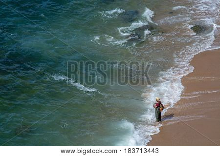 Ericeira Portugal. 15 April 2017.Fisherman fishing in a beach right in the water level. Ericeira Portugal. photography by Ricardo Rocha.