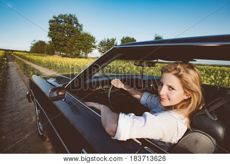 Cute young woman driving a classic car
