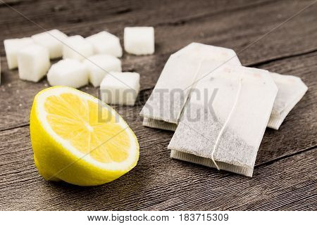 tea bagssugar and lemon on the wooden background