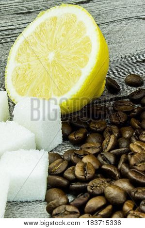 coffee grainssugar and lemon on grunge wooden background