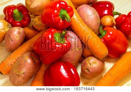 Colorful vegetables background. Carrot potatoes and bulgarian pepper. Top view close up.