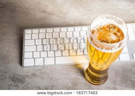Beer Next To Computer Keyboard On Concrete Table